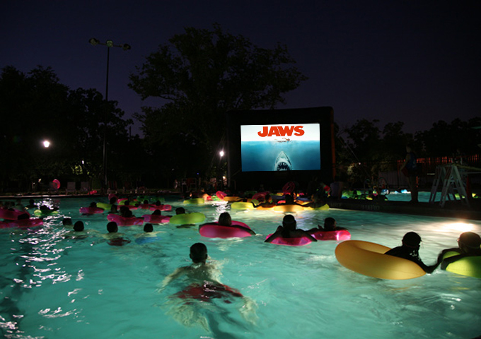 people in pool watching Jaws movie at night